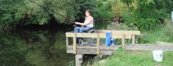 Une dame en chaise roulante qui pêche