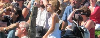 Une dame en chaise roulante parmi un public qui regarde un spectacle en plein-air
