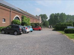 Parking en graviers et voie d'accès vers l'entrée principale
