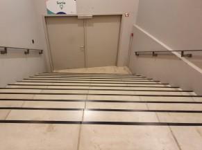 Escalier à emprunter pour les personnes valides se dirigeant vers la sortie (les personnes moins valides sont orientées vers un ascenseur pour sortir via l'entrée)
