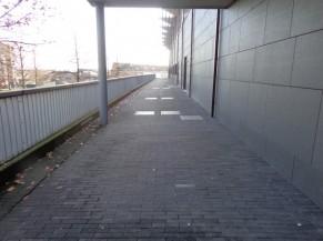 Chemin qui longe le bâtiment depuis le haut des escaliers et de la rampe et qui mène vers la porte d'entrée