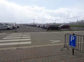 Vue sur le parking en gravier et début des parkings PMR sous abris et à proximité de l'entrée (en avant-plan de la photo)