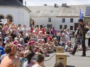 Deux artistes de rue qui font un spectacle devant un public assis par terre