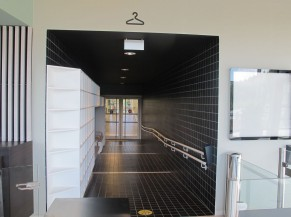Accès vestiaires: portillon PMR avec lecteur de badge accessible, couloir en pente avec main courante, bancs de déchaussage et casiers, porte zone vestaires
