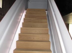 Escalier intérieur avec mains courantes et éclairage latéral au sol