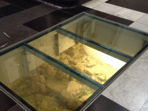 Vestiges archéologiques visibles à travers une vitre au sol