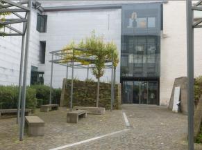Cour d'entrée: ligne guide à gauche, entrée: portes vitrées coulissantes automatiques