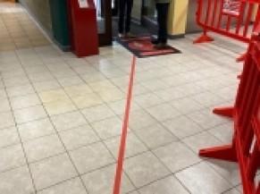 ligne guide rouge au sol depuis la porte d'entrée pour rejoindre le couloir pré-vaccination