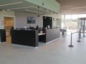 Hall d'entrée, comptoir d'accueil ouvert avec partie adaptée et couloir vers les sanitaires