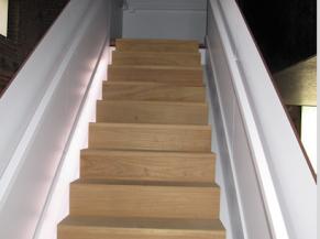 Escalier intérieur avec mains-courantes et éclairage latéral au sol