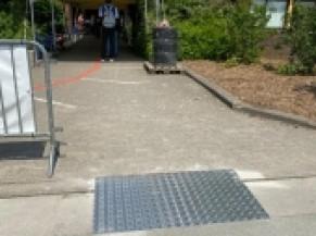 aménagement de la bordure depuis le parking et ligne guide rouge au sol vers l'entrée