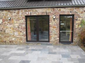 terrasse en pierres naturelles, porte d'entrée vitrée de plain-pied et porte fenêtre du salon